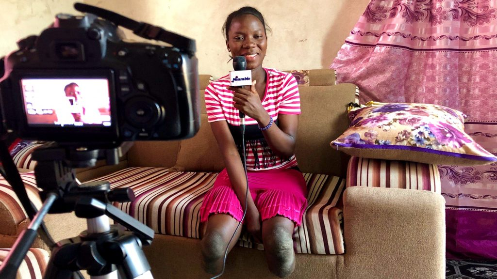 A woman with amputated legs sits on a sofa, smiling and speaking into a microphone in front of a camera.