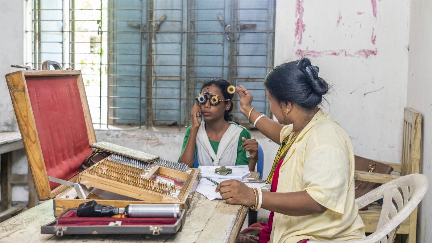 A woman checks a girl's eyes at an eye screening.