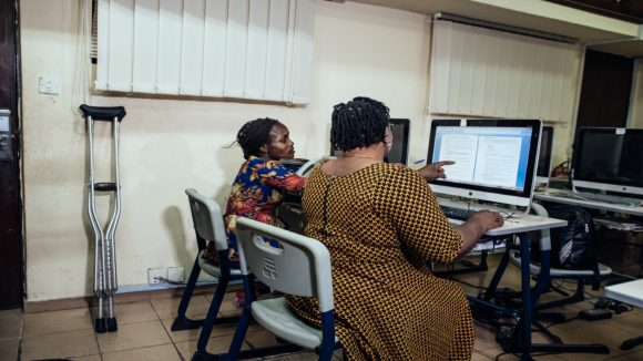 Two women sit working at a computer.