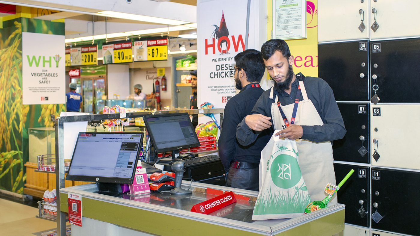 A man packs a customer's shopping bag in a supermarket.