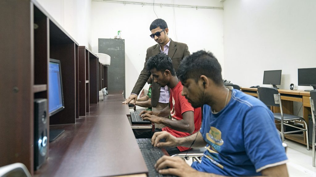 A man wearing dark glasses stands over two other men working on computers.
