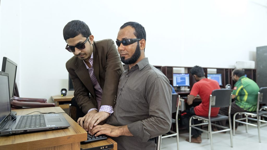 Two men with dark glasses work on a computer. One of them is helping the other use the keyboard.