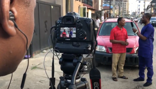 Filming an interview with a man on the streets of Nigeria.