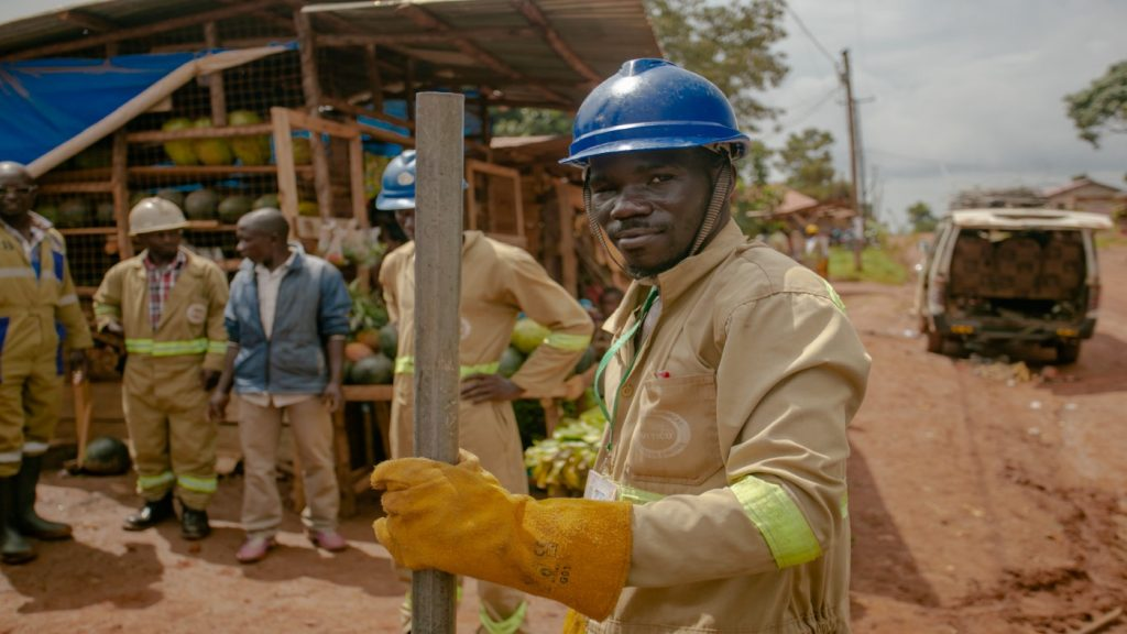 A man wearing a hard hat and overalls, looking at the camera.