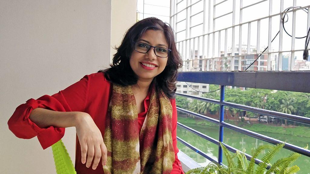 A women sitting on a balcony.