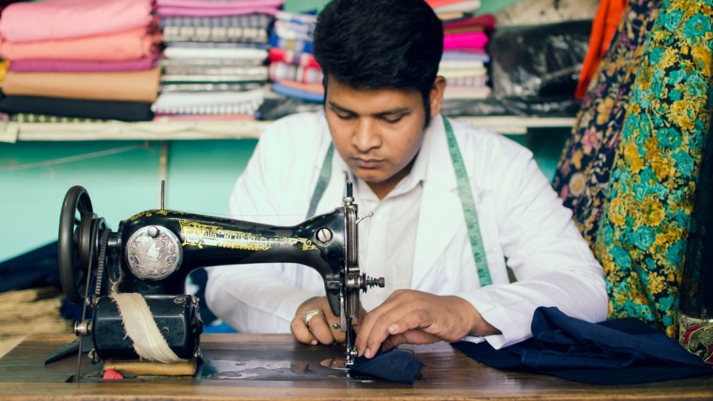 A young man uses a sewing machine.
