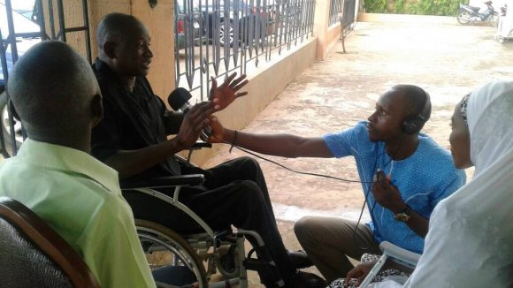 A man in a wheelchair is interviewed by a man holding a microphone and wearing headphones.