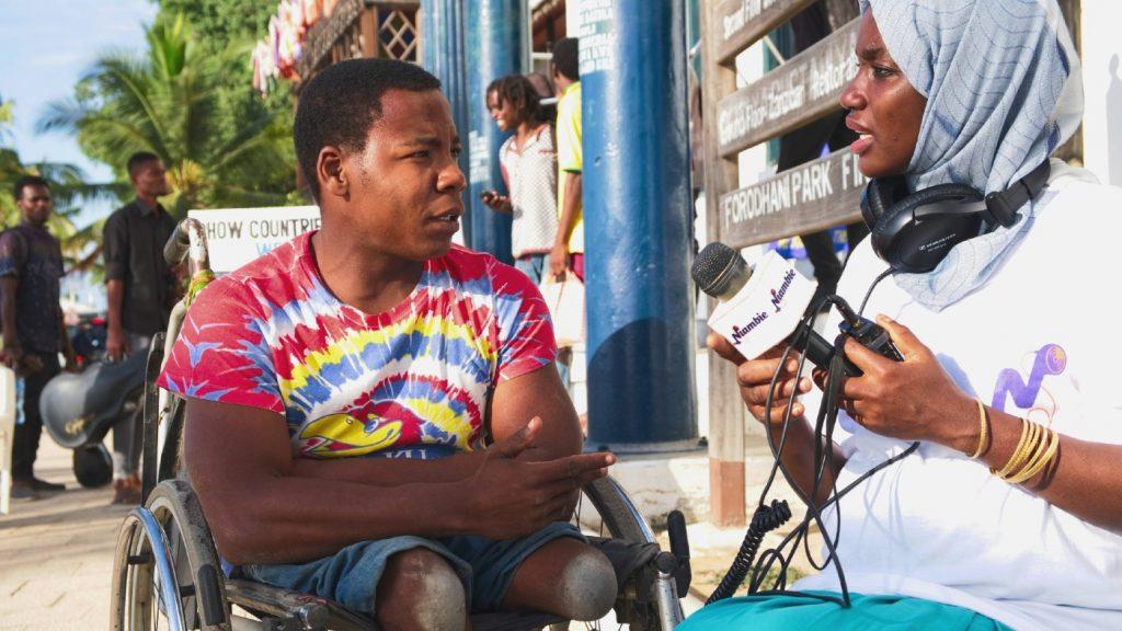 A woman interviews a man in a wheelchair who has amputated legs.