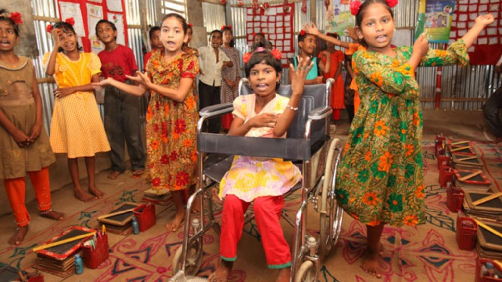 A group of girls are dancing. One of them is in a wheelchair.