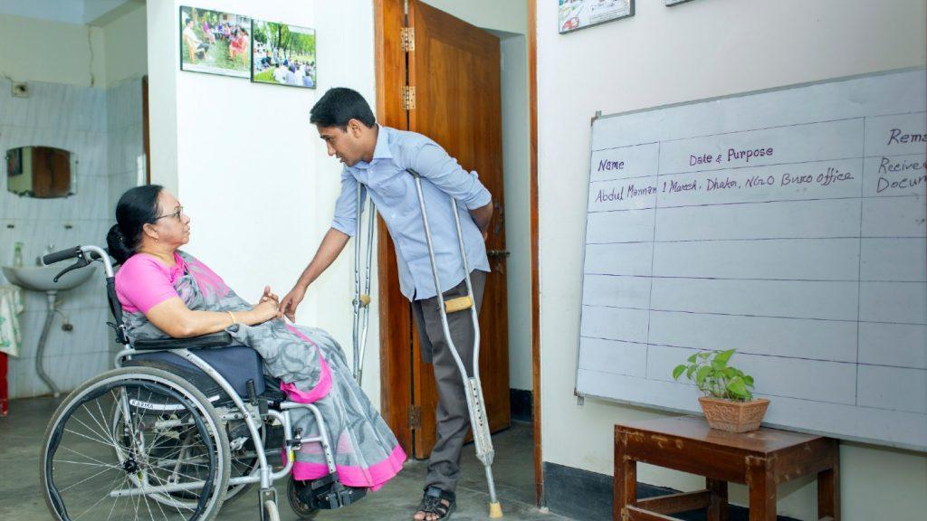 A man using a crutch greets a woman in a wheelchair.
