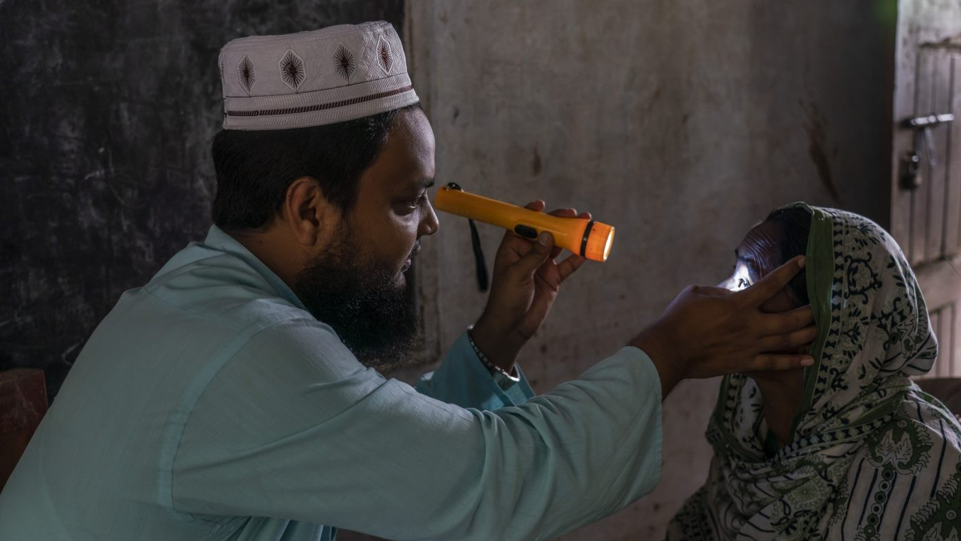 A man checks a woman's eyes using a torch.