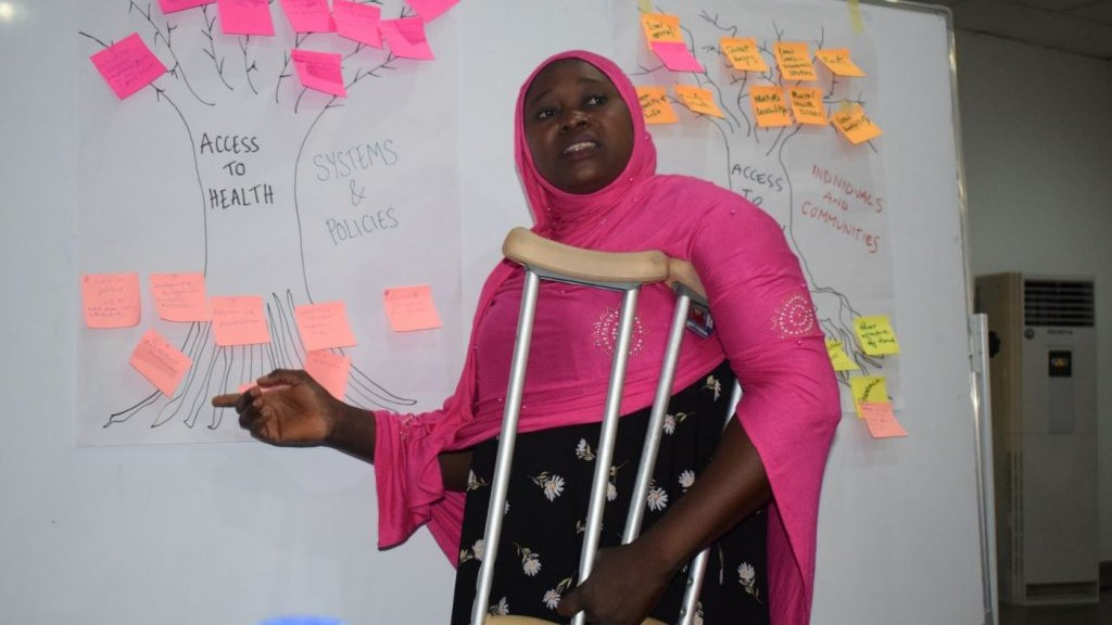 A woman with crutches stands in front of a whiteboard covered in notes.