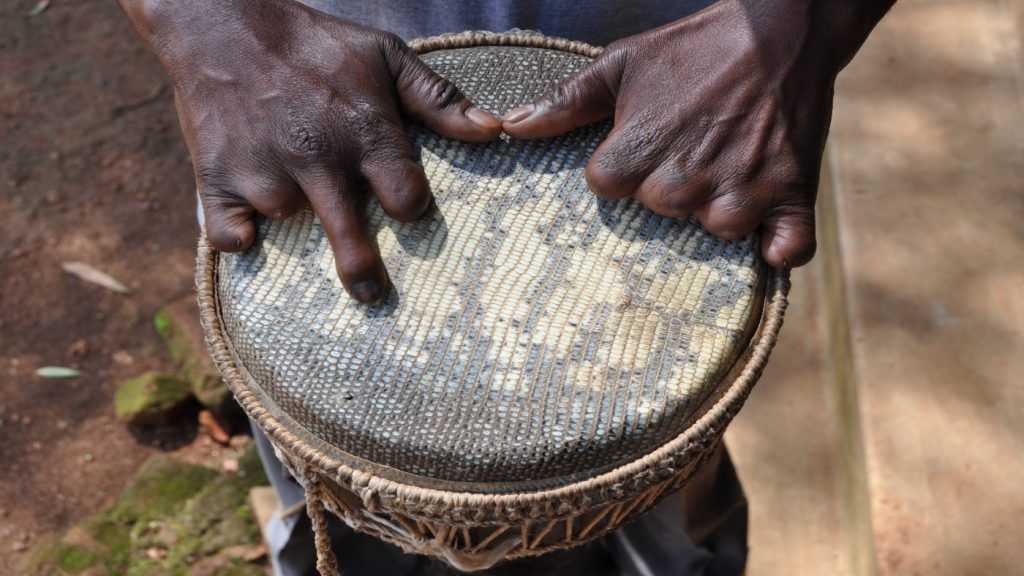 Close up of hands on a drum. The person is missing the fingers on their left hand.