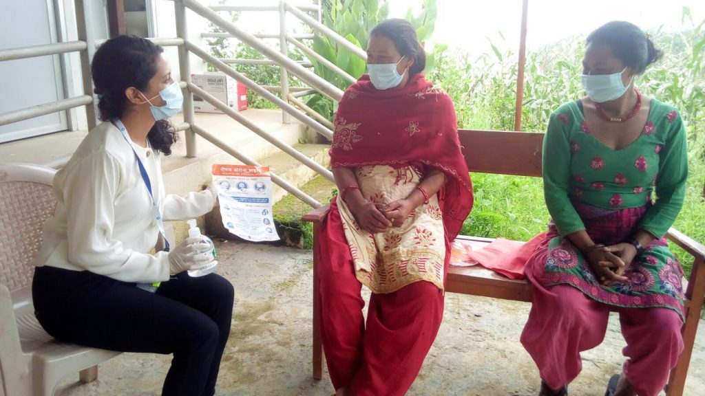 Three women sit talking in Nepal. They are wearing facemasks and one is holding a bottle of sanitiser and an information leaflet.