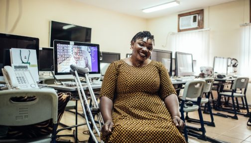 A woman in a wheelchair smiles in an office.