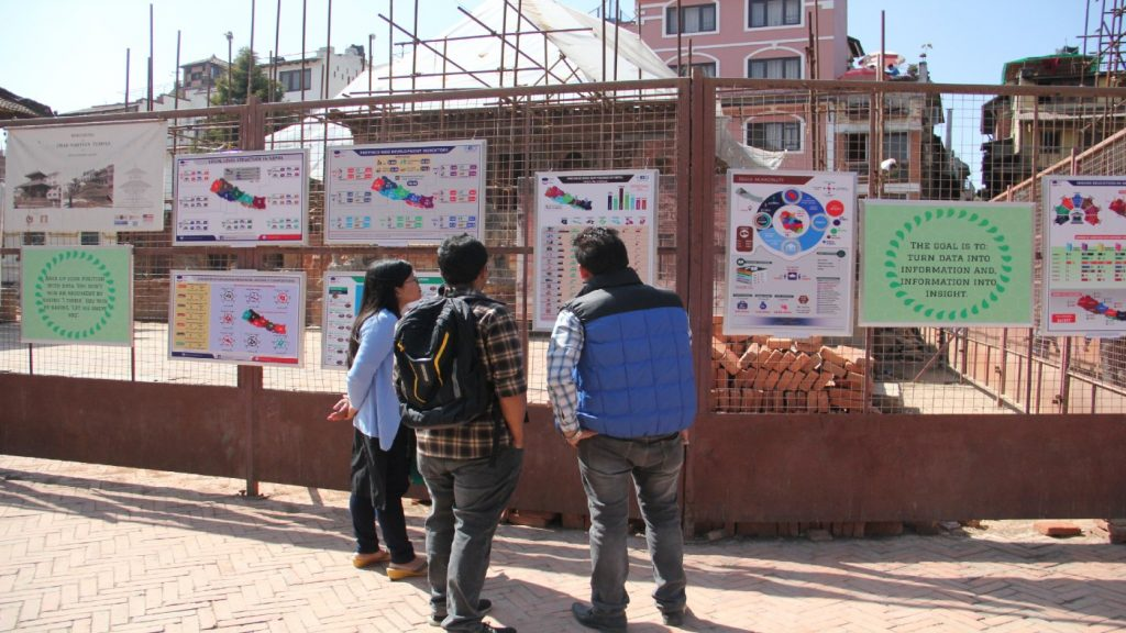 Three people look at posters on the street pinned up on a fence.