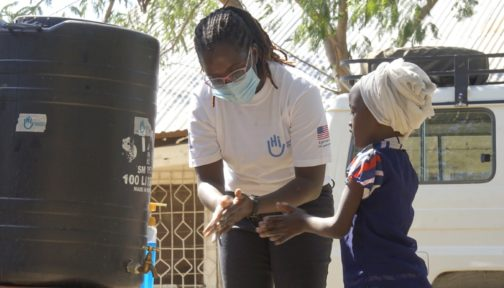 A woman shows a young girl how to wash her hands outside using a tap, in Kenya.