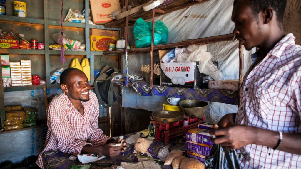 A shop owner serves a customer in his small shop in Kenya.