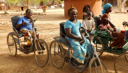 A group of women use adapted bicycles with seats to get around.