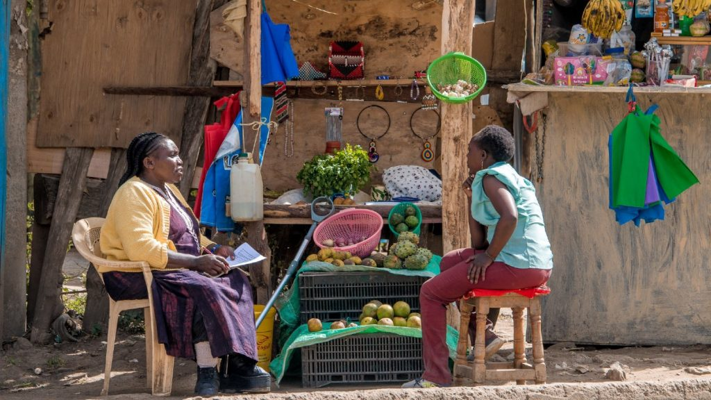 Two women speak together sitting on stools outside. They are in front of a stall selling an array of items.