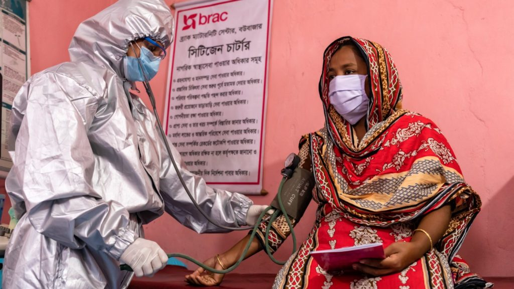 A medic in protective overalls, mask and gloves takes the blood pressure of a woman in Bangladesh.