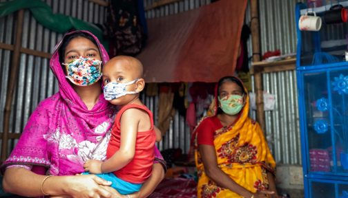 Two women and a baby wear face masks in a house in Bangladesh.