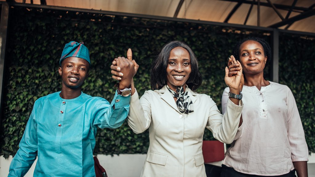 Three people holding hands and smiling at the camera in Nigeria.