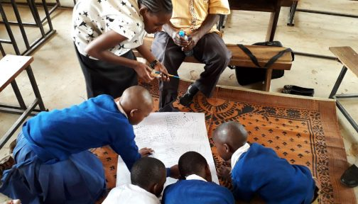 Peer research by Institute of development studies in Tanzania. Four children in school uniform sit on the floor and are writing on a large piece of paper, supervised by two adults.