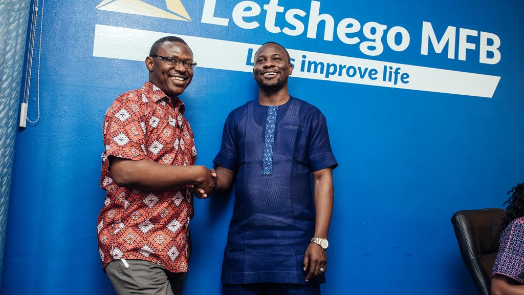 Two men shaking hands and smiling at Letshego company, Nigeria.
