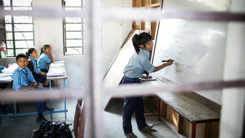 A girl writes on a whiteboard in a classroom.