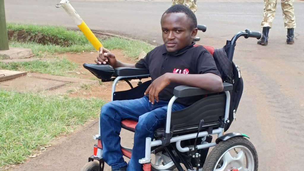 A man in an electric wheelchair posing for a photograph