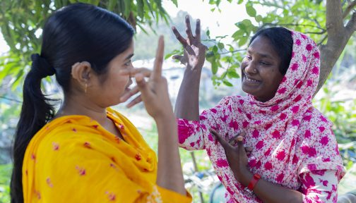 Two women in Bangladesh communicating using hand gestures.