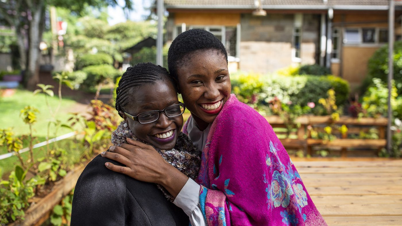 Two women smiling and hugging in Kenya.