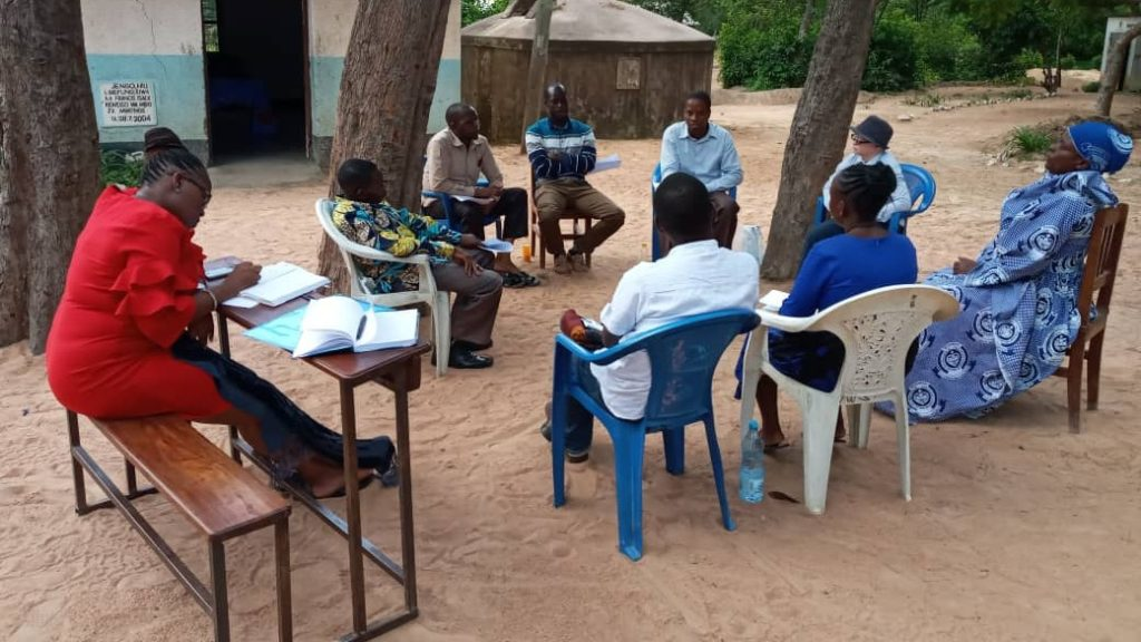 A group of nine teachers sit in a circle outside in Tanzania, having a meeting.