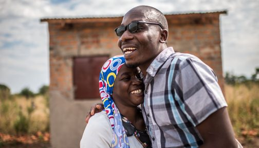 A man a women hug and laugh.