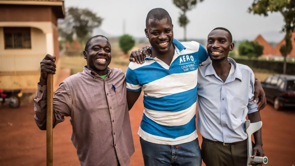 Three men stand with their arms over their shoulders, all of them are smiling.
