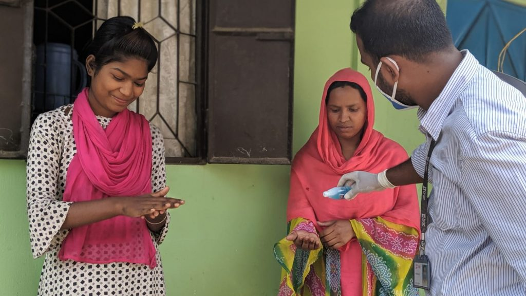 Three people in Bangladesh use hand sanitiser.