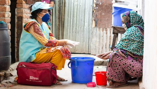 Two women sit outside in Bangladesh, one wearing a face mask and gloves demonstrates to the other woman how to wash her hands.
