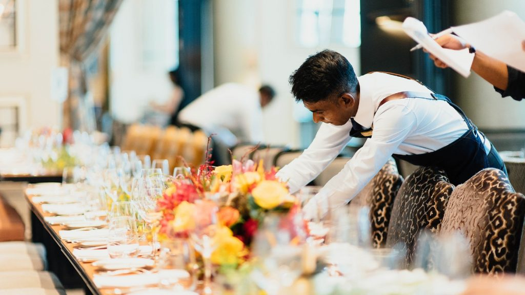 A hotel worker arranges a dinner table.
