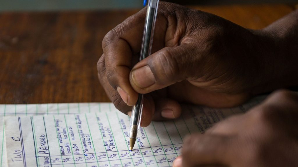 A close up image of someone writing on a piece of paper.