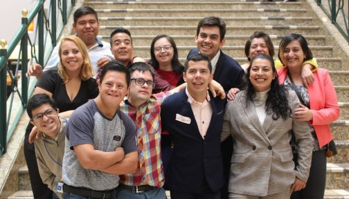 A group of people stand together outside. They are all smiling at the camera.