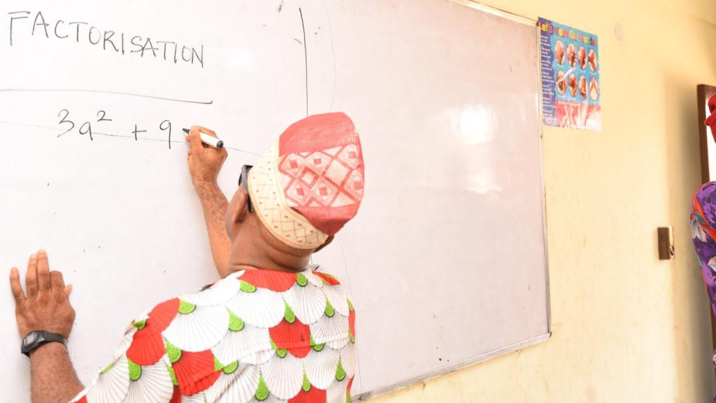 A man wearing sunglasses writes on a whiteboard.