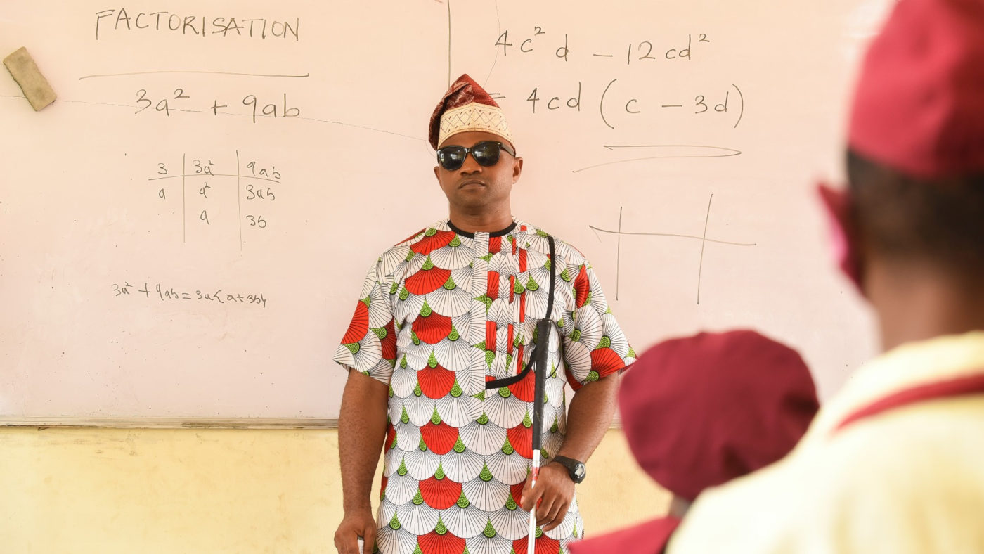A man wearing sunglasses and holding a white cane stands in front of a whiteboard at the front of a classroom. The backs of pupils head are blurred in the foreground..