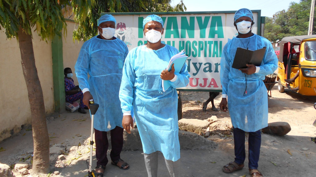 Three people wearing blue disposable overalls, blue hair nets and face masks stand in front of a hospital sign. One is wearing headphones, two are holding paper reports, and the third is holding a mearing device.
